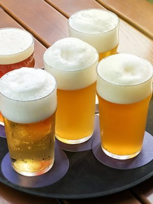 Five cold beers with frothy heads in glasses on a tray on a slatted outdoor table in a high angle close up view